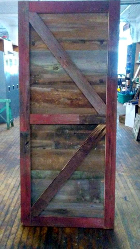 Door built by ReUse Action out of faded red barn siding